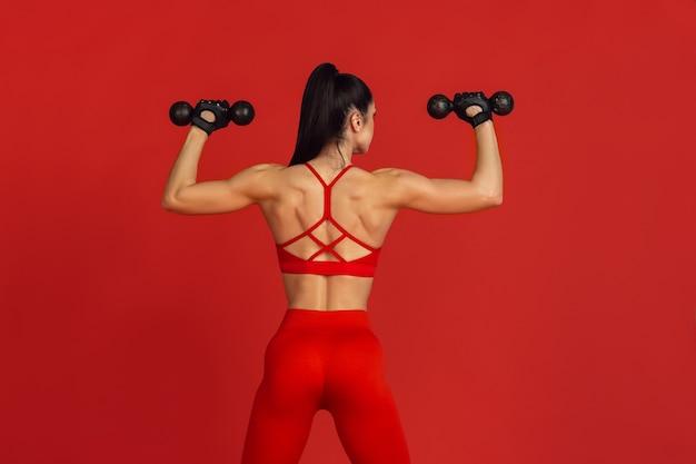 Красивая молодая спортсменка, практикующая на красной стене монохромный портрет