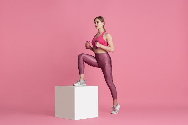 Beautiful young female athlete practicing on pink studio Free Photo