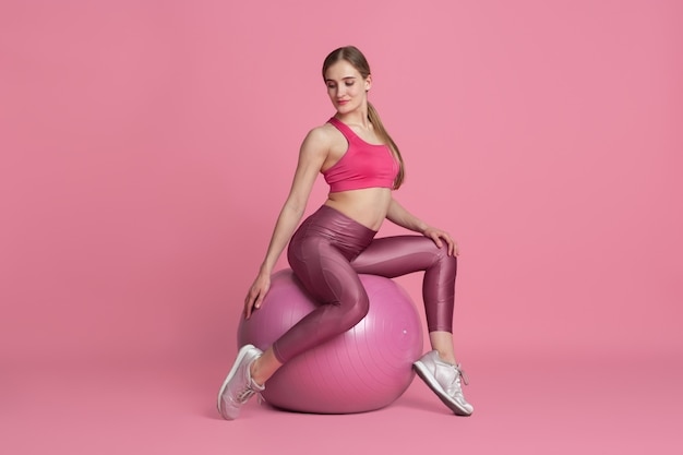Beautiful young female athlete practicing on pink studio