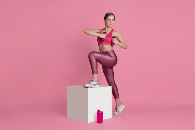 Beautiful young female athlete practicing on pink  wall monochrome portrait Premium Photo