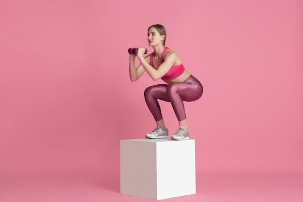 Beautiful young female athlete practicing on pink  wall monochrome portrait
