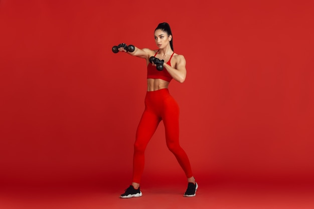 Beautiful young female athlete practicing on red studio wall