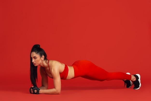 Bella giovane atleta femminile che si esercita sul ritratto monocromatico della parete rossa