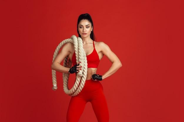 Bella giovane atleta femminile che si esercita su red