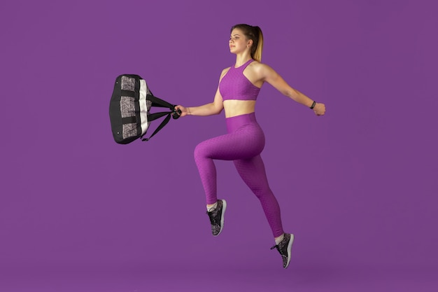 Beautiful young female athlete practicing in studio