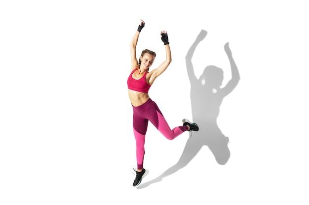 Bella giovane atleta femminile che pratica su uno spazio bianco, ritratto con le ombre