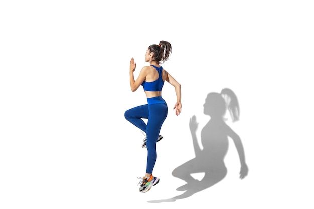 Beautiful young female athlete practicing on white studio background with shadows