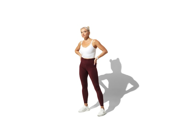 Beautiful young female athlete practicing on white studio wall, portrait with shadow.