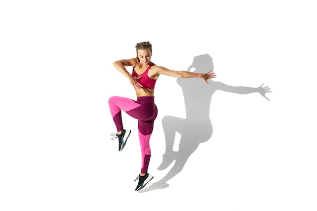Beautiful young female athlete practicing on white studio wall with shadows
