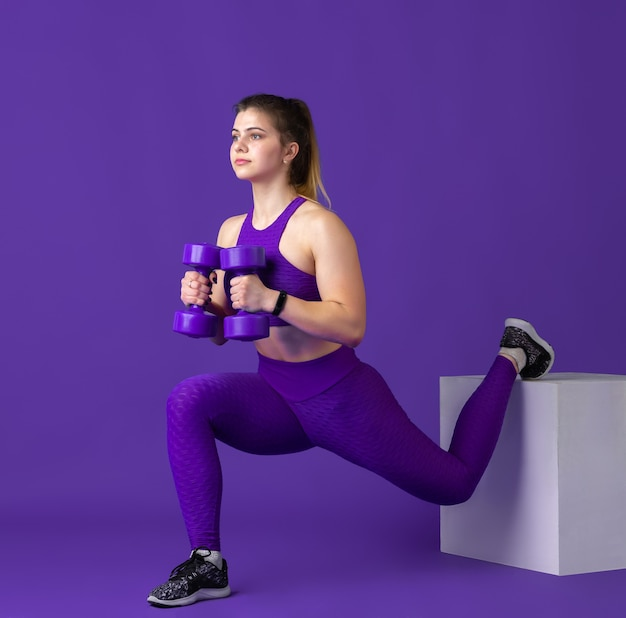 Beautiful young female athlete practicing with weights