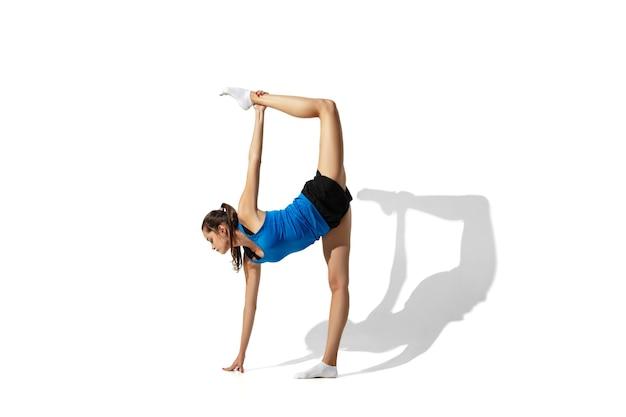 Bello giovane atleta femminile che allunga, formazione su uno spazio bianco, ritratto con le ombre