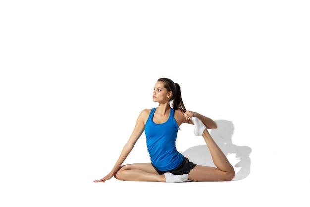 Beautiful young female athlete stretching on white studio background with shadows