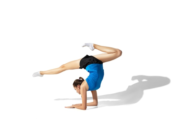 Beautiful young female athlete stretching on white with shadows