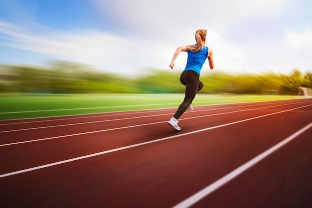 아름다운 젊은 여성 금발 운동선수가 흐릿한 배경에서 트랙 백뷰를 달리고 있습니다. 운동 선수가 비행 중에 경기장 점프 사진 주위를 실행합니다. 체육 실기.