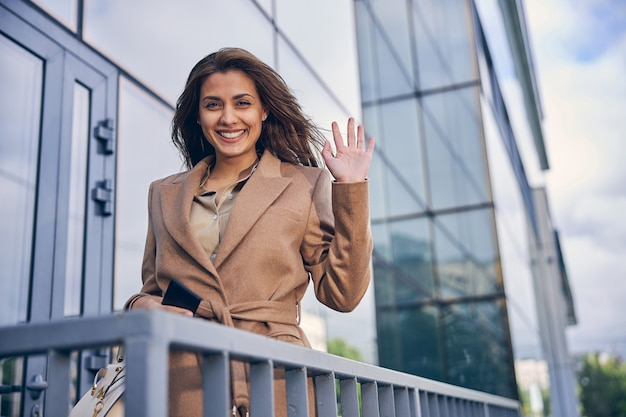 Beautiful young female in brown coat waving her hand while staying outside near business center