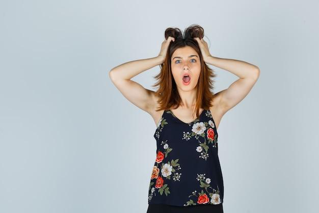 Bella giovane femmina che stringe la testa con le mani in camicetta e sembra scioccata