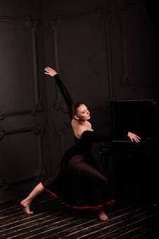 Beautiful young female classical ballet dancer on pointe shoes wearing a black leotard and skirt on a brick background