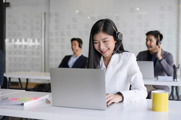 Beautiful young female customer services agent with headset working in a call center office.
