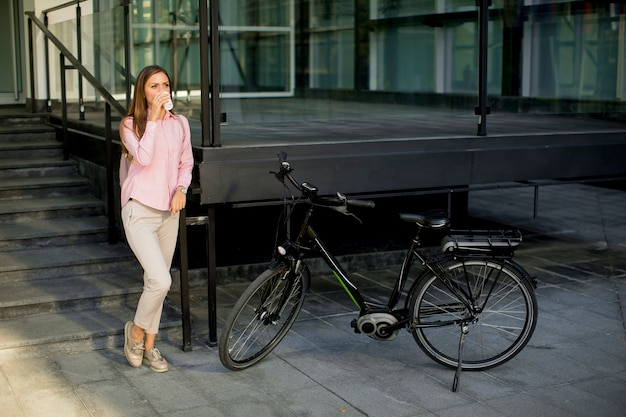 Beautiful young female cyclist drinks warm coffee from a cup by the electric bicycle in the urban environment