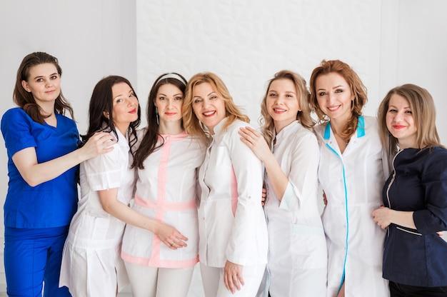 白い壁の背景にポーズをとって白い制服を着た美しい若い女性医師。チームの団結のしるしとして抱き締める女性たち。