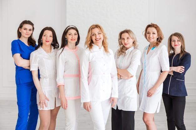 白い壁の背景にポーズをとって白い制服を着た美しい若い女性医師。