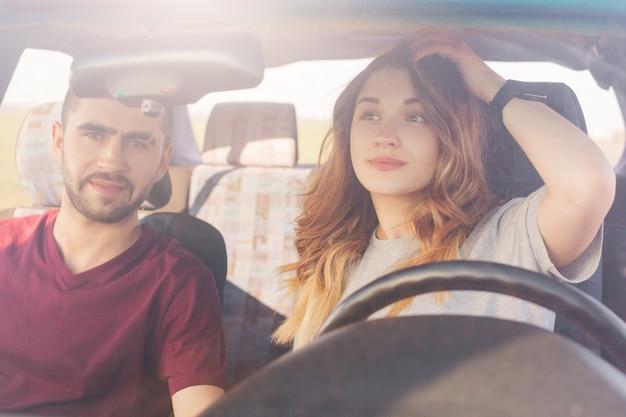 美しい若い女性ドライバーは車の鏡を見て、夫またはボーイフレンドの隣に座って、一緒に旅をし、田舎道を運転します。家族のカップルが自動車ディーラーで新しい車を選ぶ