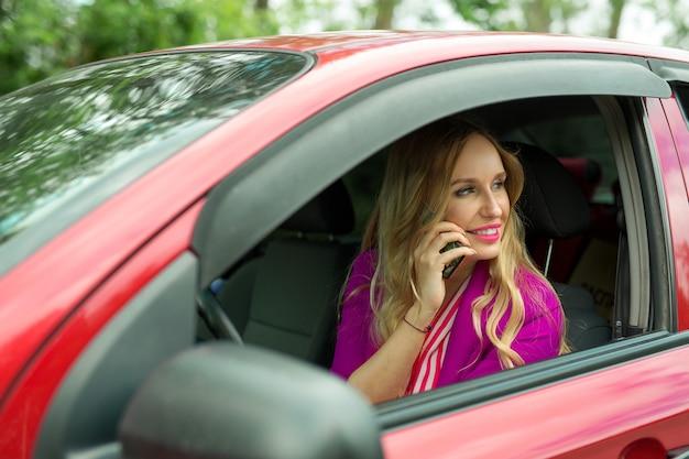 휴대 전화로 차를 운전하는 아름 다운 젊은 여성