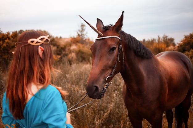 森の森のニンフで休んでいる彼女の馬をかわいがる長い暗いウェーブのかかった髪を持つ美しい若い女性のエルフ彼女の馬の世話をするペットの愛の動物の調和思いやりのある所有者優しい生き物の神話