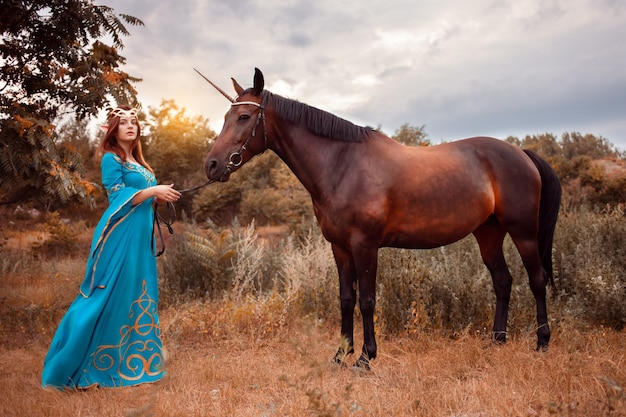 Beautiful young female elf with long dark wavy hair petting her horse resting in the woods forest nymph stroking her horse care pet love animals harmony caring owner gentle creature myth