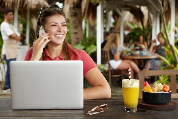 Красивая молодая женщина-предприниматель разговаривает по мобильному телефону со счастливым взглядом, сидя за деревянным столом с коктейлем и открытым универсальным портативным компьютером