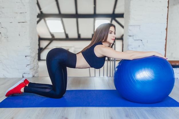 Красивая молодая женщина упражнениями с мячом пилатес в тренажерном зале
