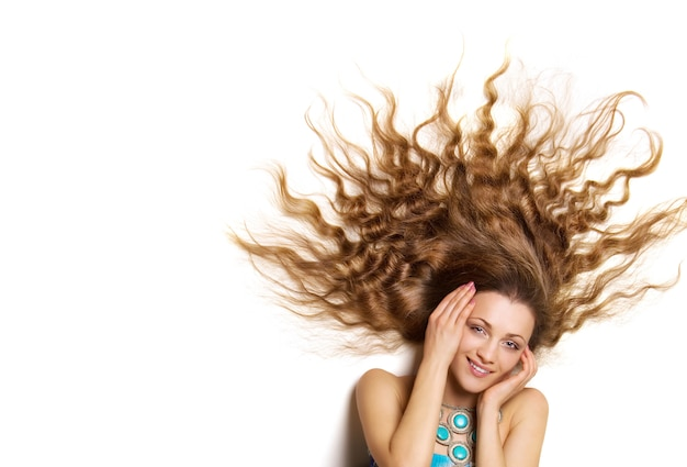 Beautiful young female face with long blond curly hair