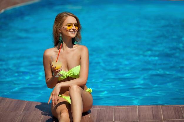 Красивая молодая женщина в купальнике возле бассейна