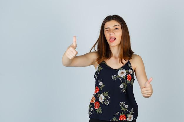 두 엄지 손가락을 보여주는 블라우스에 아름 다운 젊은 여성