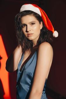 Красивая молодая женщина в новогодней шапке смотрит в камеру, стоя в темной комнате