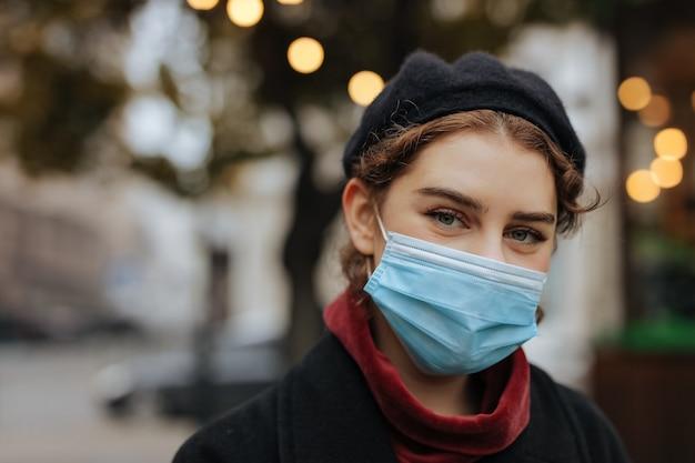 市内中心部に立っている医療フェイスマスクの美しい若い女性。コロナウイルス発生時の健康保護
