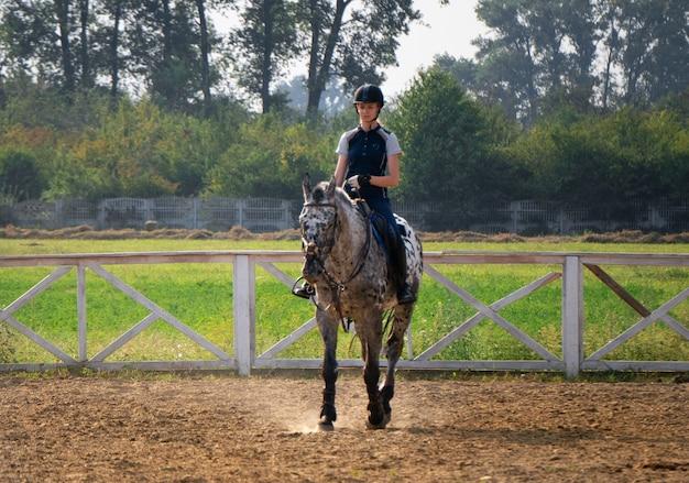 屋外の馬に乗った美しい若い女性騎手。女性アスリートはオープンマネゲで馬に乗る