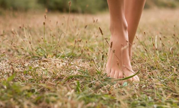 Красивые молодые женские ножки, идущие по траве летом
