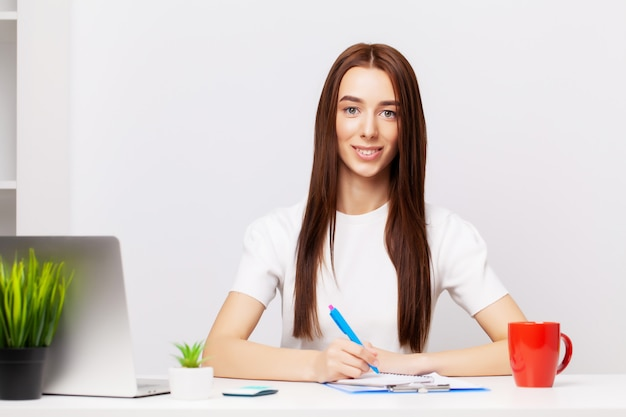 Beautiful young female manager working with documents in the office