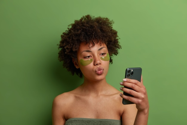 Beautiful young female model with curly afro hair, applies hydrogel green patches to reduce problem dark circles under eyes, takes selfie on mobile phone, keep lips rounded, wrapped in bath towel