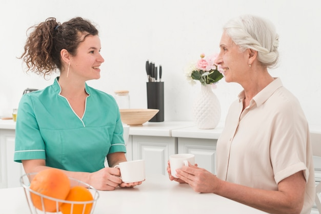 Beautiful young female nurse having coffee with senior woman
