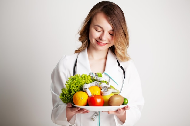 Beautiful young female nutritionist with fresh vegetables and fruits