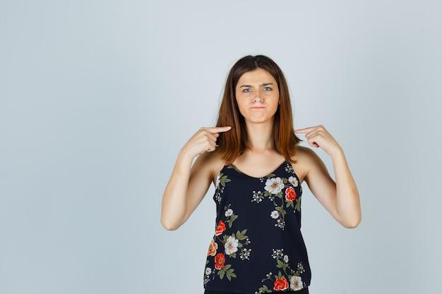 Bella giovane donna che punta a se stessa, stringendo le labbra mentre si acciglia in camicetta