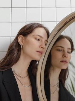Bella giovane femmina in posa in specchio