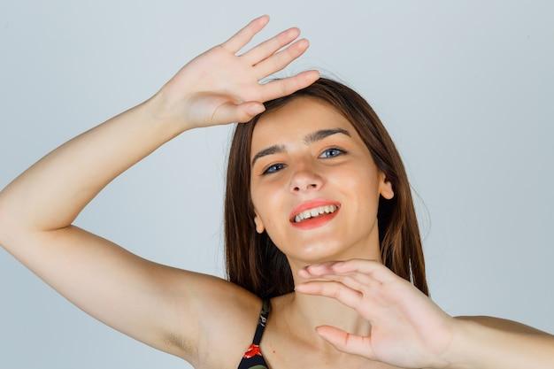 Красивая молодая женщина позирует с руками вокруг головы в блузке и выглядит весело