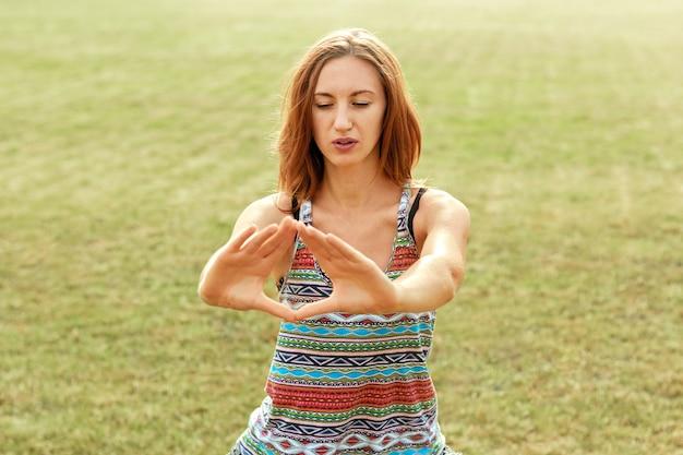 美しい若い女性は、緑の自然の中でヨガのポーズでリラックスします。ヨガをやっている美容女性。健康とヨガのコンセプトです。フィットネスとスポーツ