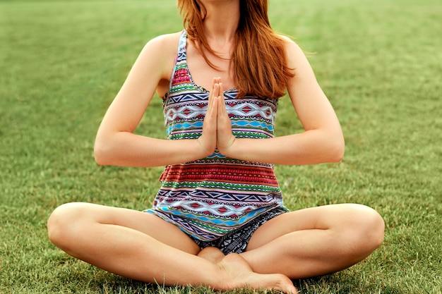 Красивая молодая женщина расслабляется в позе йоги в зеленой природе.