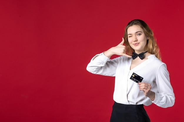 Bella giovane farfalla server femminile sul collo e tenendo la carta bancaria facendo mi chiama gesto su sfondo rosso