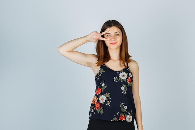 Bella giovane femmina che mostra il segno a v vicino all'occhio in camicetta e che sembra allegro