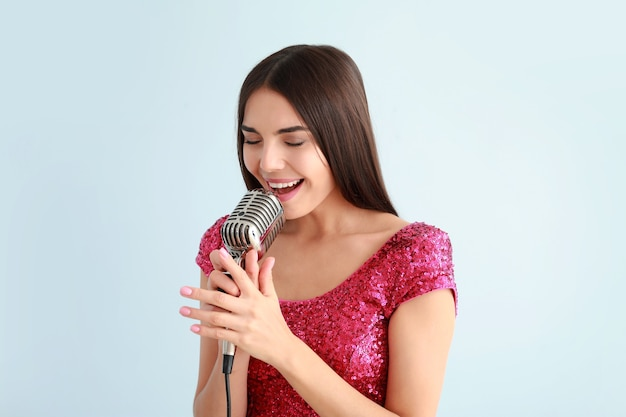Beautiful young female singer with microphone on light surface